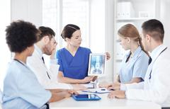Group of doctors with x-ray on tablet pc at clinic Stock Photos