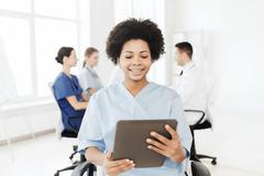 Happy nurse with tablet pc over team at hospital Stock Photos