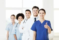 Happy doctors showing thumbs up at hospital Stock Photos