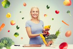 smiling young woman cooking vegetables at home - stock photo