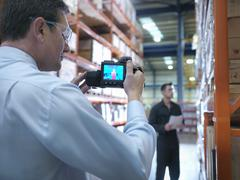 Office worker taking thermal image with camera in factory - stock photo