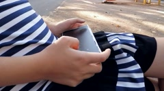 Hands of the girl who plays on the smartphone Stock Footage