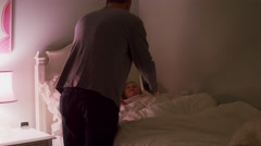 A father tucks his daughter into bed Stock Footage