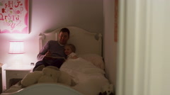 A father reads his daughter a bedtime story Stock Footage