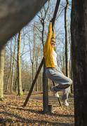 Young woman dangling from pole on forest assault course - stock photo