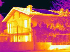 Thermal image of a house with solar cells on the roof. Absorbing the light - stock photo