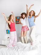 Happy friends or teen girls having fun at home Stock Photos