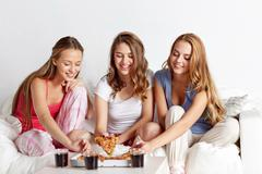 Happy friends or teen girls eating pizza at home Stock Photos