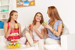 Happy young women drinking tea with sweets at home Stock Photos