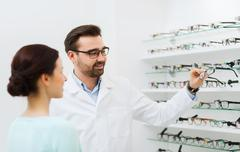 optician with glasses and woman at optics store - stock photo