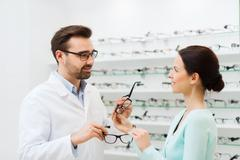 woman and optician showing glasses at optics store - stock photo