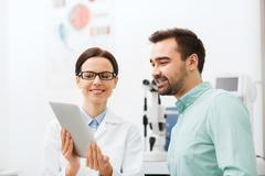 optician with tablet pc and patient at eye clinic - stock photo