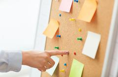hand pointing to cork board with stickers and pins - stock photo