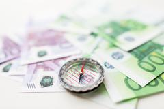 Close up of compass and euro money on table Stock Photos