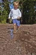 Young boy splashing in muddy puddle Stock Photos