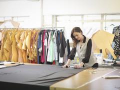 Fashion designer measuring fabric in fashion design studio Stock Photos