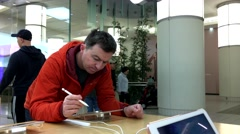 People playing new ipad with pen inside Apple store Stock Footage