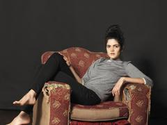 Young woman sitting in armchair Stock Photos