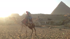 Female tourists riding a camel at Giza pyramids at sunset - stock footage