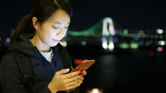 Woman use cellphone at night in Odaiba, Tokyo Stock Footage