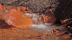 Closeup-Low angle-Small stream over orange rocks Stock Footage