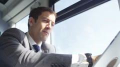 4k Businessman working on digital tablet & drinking coffee on train journey - stock footage