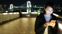 Woman with mobile phone at night in Odaiba, Tokyo Stock Footage