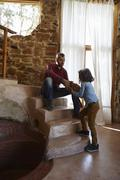 Young girl handing log to her father on sitting room stairs Stock Photos