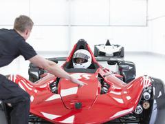 Engineer and racing car driver in supercar in sports car factory Stock Photos