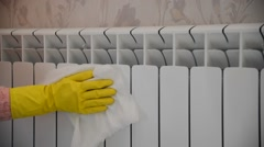 Female hand in  rubber glove cleans heating radiator Stock Footage