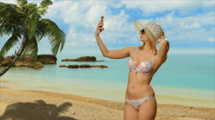 Girl blonde in swimsuit  posing near the sea makes selfie phone Stock Footage