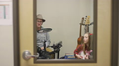 View through the door of a young girl taking guitar lessons Stock Footage