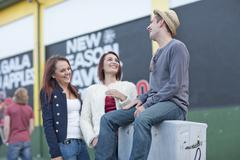 Two young women and mid adult man flirting on city street - stock photo