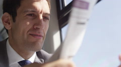 4k Business executive reading newspaper & drinking coffee on commuter train Stock Footage