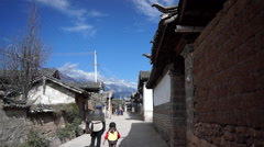Elderly woman with little girl walking in Lijiang ancient town Stock Footage