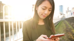 Woman using cellphone under sunlight at evening Stock Footage