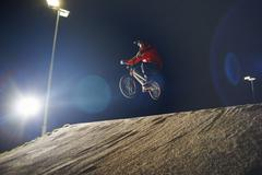 BMX-cyclist jumps his bike at night time Stock Photos