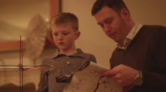 A father and son reading instructions and building a plastic toy Stock Footage