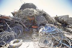 Heap of coiled and tangled cables in scrap metal yard Stock Photos