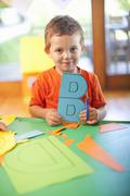 Portrait of boy with letter B at nursery school Stock Photos