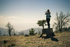 Rear view of mid adult woman photographing from tree trunk, Lake Arrowhead, Stock Photos