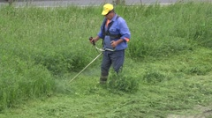 Mature man trimming grass 4k, UHD, zoom out Stock Footage