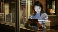 Young woman using tablet pc at coffee shop at night Stock Footage