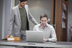 Two men in office, one using laptop Stock Photos