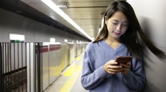Woman typing message on cellphone at underground subway - stock footage