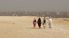 Zoom Out - Tourists walk in the Desert with the City of Giza in the Background Stock Footage