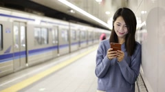 Woman use of smartphone at subway station - stock footage