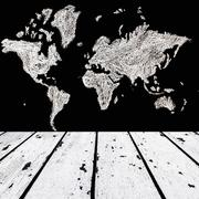white wooden floor and map of the world on black chalk board front - stock photo
