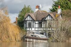 Windsor, UK - February 11, 2014: Rising water levels push a motorboat against a  - stock photo