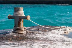 Rusty mooring bollard with ship ropes and  clear turquouse sea ocen water on Stock Photos